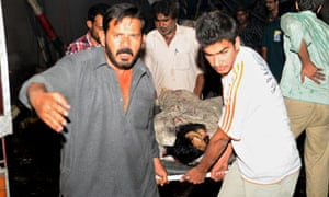 Pakistani rescuers evacuate a victim from site of blast in Karachi