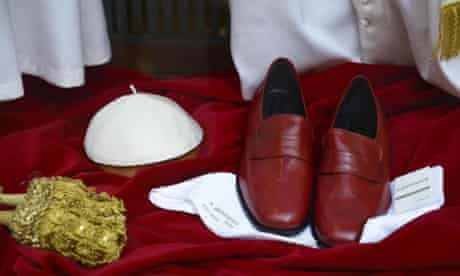 Wanted: one very religious man, uniform supplied. A a white mitre, a band with gold tassels, a cord and a pair of red leather shoes for the future Pope in the window of the Italian taylors shop Gammarelli, behind the Pantheon, Rome, Italy.