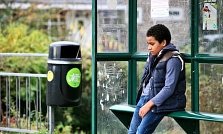 Little boy sitting at bus stop