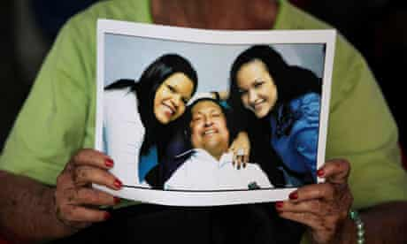 A Venezuelan woman holds a photograph of Hugo Chávez in hospital with his daughters at his side