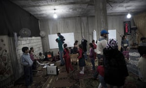 Syrian children are seen attending a makeshift school in the protective environment of a cellar of a building in the eastern town of Deir Ezzor on 19 February.