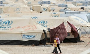 Syrian refugee children walk along tents at the Za'atari refugee camp in the Jordanian city of Mafraq.