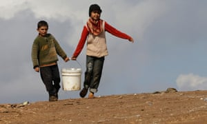 Syrian children carry a bucket of water at the Atmeh camp, in the northern Syrian province of Idlib, Syria.