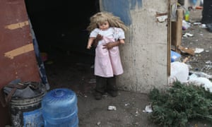 Mirna Guadelupe, 4, plays in front of her modest home with a doll found at the Tirabichi garbage dump.
