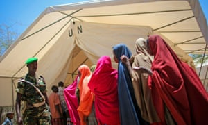 A Burundian soldier walks past Somali women queuing for medication outside a tented pharmacy in Mogadishu. Since Burundi first deployed it's troops to Somalia in 2007 their free medical facilities have been a lifeline for thousands of civilians that were caught up and injured during fighting with the Al-Qaeda affiliated extremist group Al Shabaab in and around Mogadishu.