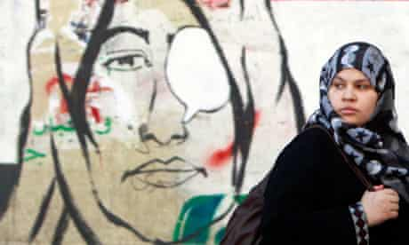 A woman walks past a mural depicting a woman with eye patches near Tahrir Square in Cairo