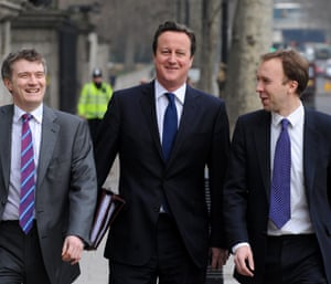 Does that mean there's good news on the economy? Ahead of his big speech on the economy, David Cameron walks with his aides from 10 Downing Street to the Houses of Parliament for the weekly Prime Minister's Questions.