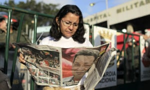 A woman reads a newspaper with the picture of late Venezuelan President Hugo Chavez on the front page at a gathering at the military hospital in Caracas, Venezuela.