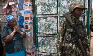 A woman waits outside a vote tallying centre with a Kenyan police officer guarding the gate at Mathare slum in Nairobi. Kenyan authorities were racing to gather final election results after a partial count gave the lead to Uhuru Kenyatta, who is currently wanted in The Hague over violence during the last election.