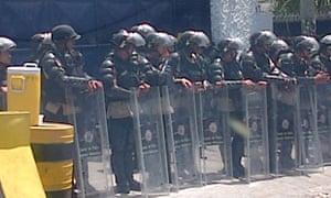 Riot police protect the private TV station Globovision.