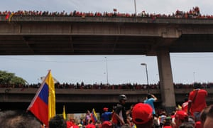 Supporters stand on highway overpasses to get a view of the flag-draped coffin containing the body of Venezuela's late President Hugo Chavez being taken from the hospital, where he died on Tuesday, to a military academy in Caracas, Venezuela, Wednesday, March 6, 2013. Seven days of mourning were declared, all schools were suspended for the week and friendly heads of state were expected for an elaborate funeral Friday. (AP Photo/Rodrigo Abd)