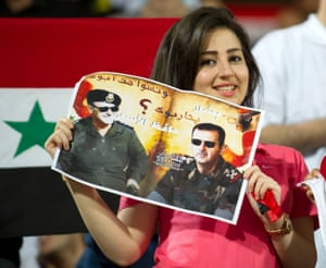 A woman holds a poster of Syrian President Bashar al-Assad during the AFC Cup soccer match between Syria's Al Shorta and Kuwait's Al Qadsia in Kuwait City.