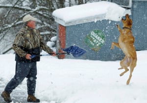 Bill Groves plays with his dog Red while shoveling snow during a massive blizzard near Mt. Jackson, Virginia. Washington and its suburbs face what could be their heaviest snowfall in two years, as a fierce storm headed east after blanketing the Midwestern United States, snarling traffic and causing hundreds of flight cancellations.