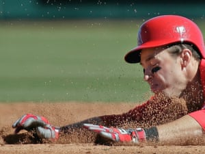 Dirt flies as Los Angeles Angels' Trent Oeltjen slides into second base trying to stretch a single into a double during the third inning of an exhibition baseball game against Italy in Tempe, Arizona, United States. Oeltjen was tagged out on the play.