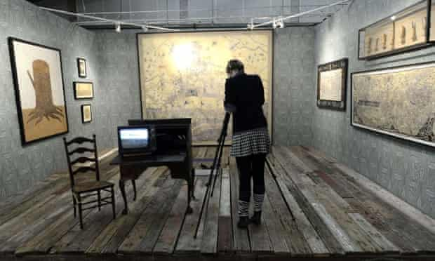 A woman takes photos of the work of artist  Duke Riley during the press preview  at the 2013 Armory Show.