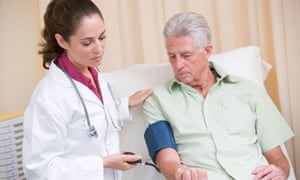 Doctor checking man's blood pressure in exam room