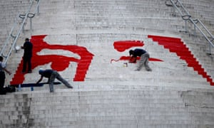 Workers paint a mural of the eyes of Venezuela's late President Hugo Chavez