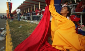Chavez funeral: A woman keeps warm wrapped in the national flag at funeral of Hugo Chavez