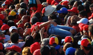 A supporter of Venezuela's late president Hugo Chavez is lifted out of the crowd after fainting while waiting for a chance to view his body at the military academy in Caracas on 8 March 2013.