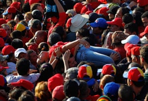 Hugo Chavez funeral: A supporter of Hugo Chavez is lifted out of the crowd after fainting
