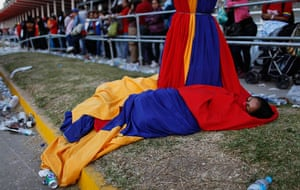 Hugo Chavez funeral: A woman wrapped in national flag colours of Venezuela's flag sleeps