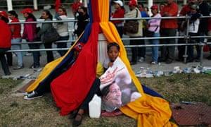 Chavez funeral: A woman holds a poster of Venezuela's late Hugo Chavez under Venezuelan flag