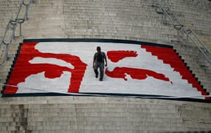 Hugo Chavez funeral: A man walks a mural of the eyes of the late Hugo Chávez on the stairs