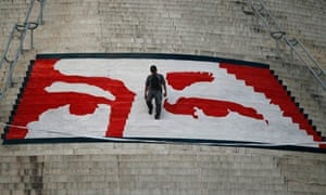Chavez funeral: A man walks on a mural of the eyes of the late president Hugo Chávez at the El Calvario monument.