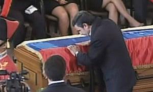 Mahmoud Ahmadinejad kisses Hugo Chavez's coffin.
