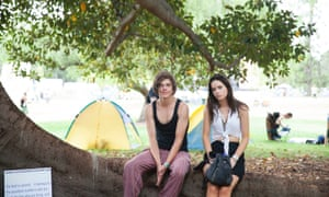 Locals Brandon and Charlotte sit under a tree in Adelaide's botanical gardens, where the festival is being held