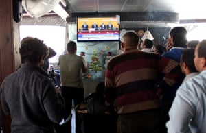 Men in a coffee shop in Port Said, Egypt, watch the televised court verdict