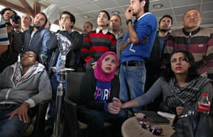 Egyptians in a coffee shop in Port Said watch the court verdict on television