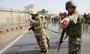 An Afghan soldier directs a firefighter to hose down the scene of a suicide bomb attack in Kabul