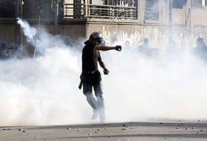 Port Said: A riot policeman throws a tear gas canister