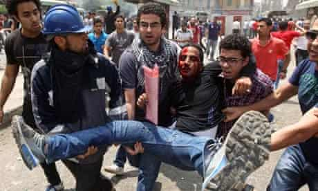 Egyptian anti-military protesters evacuate a demonstrator