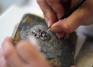 FTA: Christopher Furlong: A craftswoman hand paints enamels on a badge