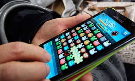 A commuter playing a game on a smartphone