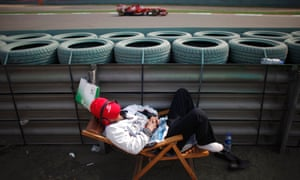 Obviously some effective ear defenders in use here as a race marshall sleeps as Ferrari Formula One driver Fernando Alonso of Spain drives past him during the second practice session of the Chinese F1 Grand Prix at the Shanghai International circuit.