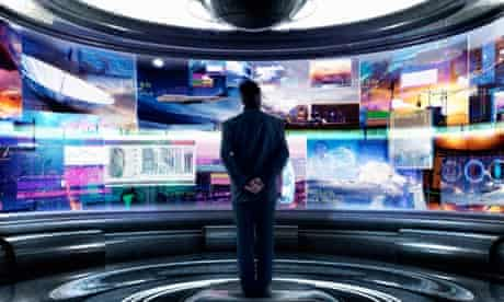 A man stands in front of several computer screens