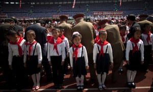 North Korean children wait while officers tie red bandanas around their necks during a ceremony to induct children into the Korean Children's Union, the first political organisation for North Koreans, at a stadium in Pyongyang.