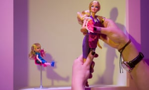 A woman holds a Barbie doll at Barbie: the Dreamhouse Experience in Berlin, Germany.