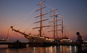 A man watches the sunrise with the sail training vessel ARM Cuauhtmoc pictured in the foreground in Veracruz harbour, Mexico. The vessel is scheduled to embark on a circumnavigation of the world.