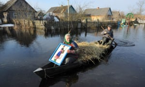 A man paddles on a boat with his wife in a flooded street during spring flood in a village of Vereshitsa near Pripyat river, Belarus
