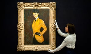 A Sotheby's employee holds a painting by Amedeo Modigliani called L'Amazone which is up for auction in New York in May.