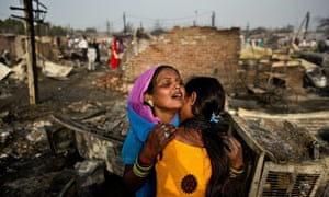 Two women weep as they stand near their burnt shanty in Bawana on the outskirts of New Delhi.  A fire broke out in a slum with one person reported dead and another five injured.