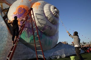 Coachella: Artists paint a giant snail statue at the Festival in Indio, California