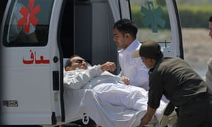Former Egyptian president Hosni Mubarak is escorted from a helicopter ambulance in Cairo