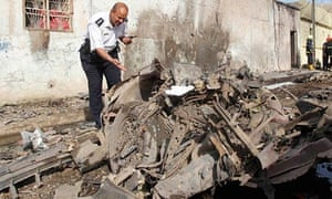 A member of the Iraqi security forces inspects the site of a car bomb attack in Kirkuk