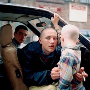 Big Picture - Rob Bremner: skinhead boy sitting in car with another boy holding young child