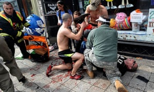 Bystanders tend to an injured man following the Boston Marathon explosions.